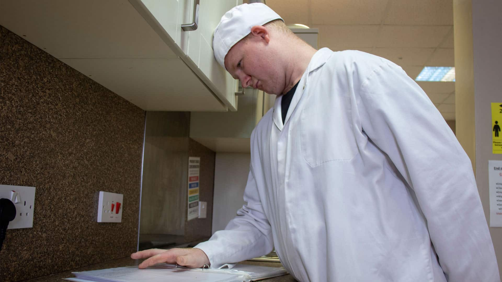 A service user reading some instructions in the Magpies' kitchen