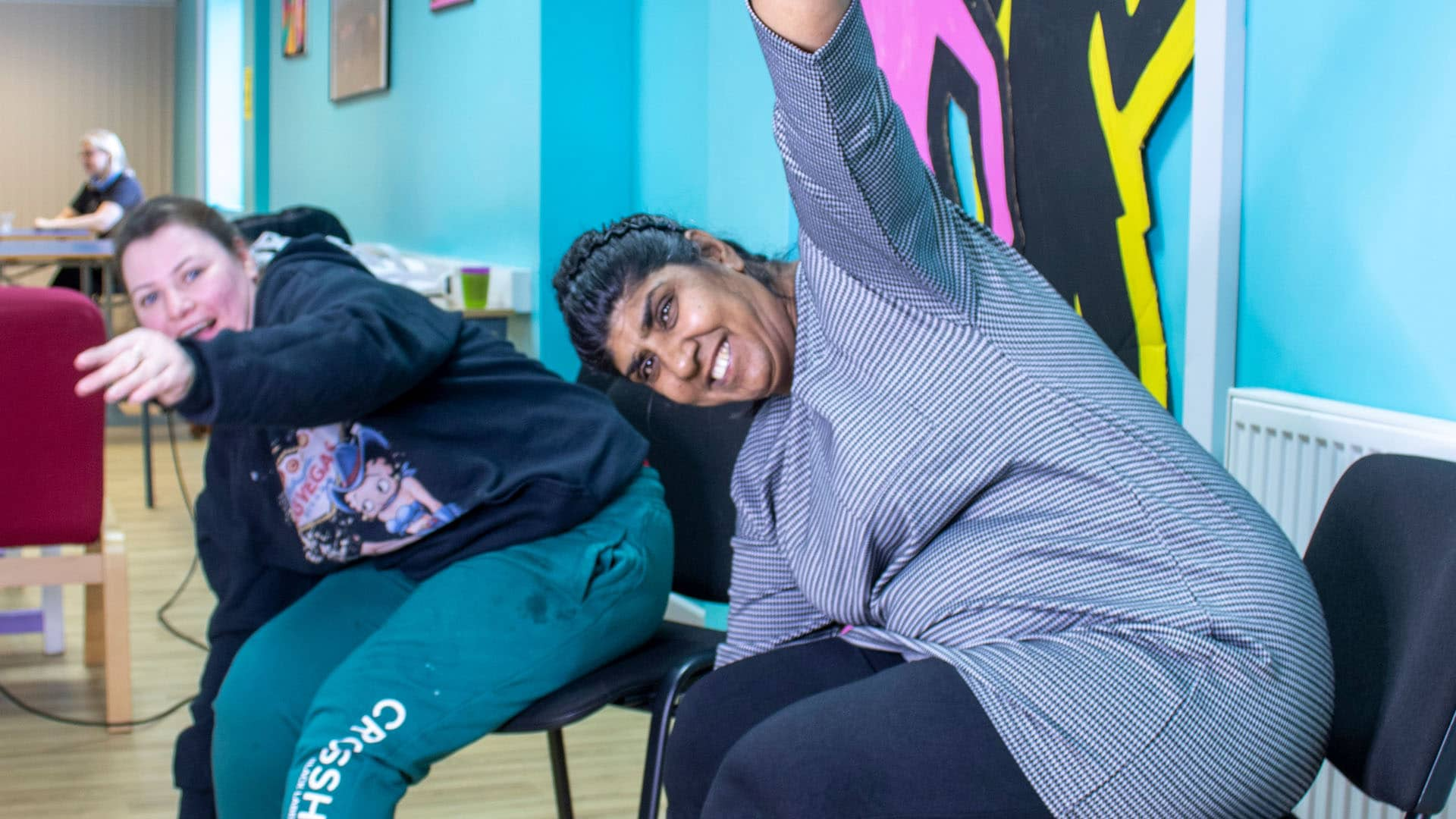 Two service users sat in chairs doing stretches with big smiles on their faces