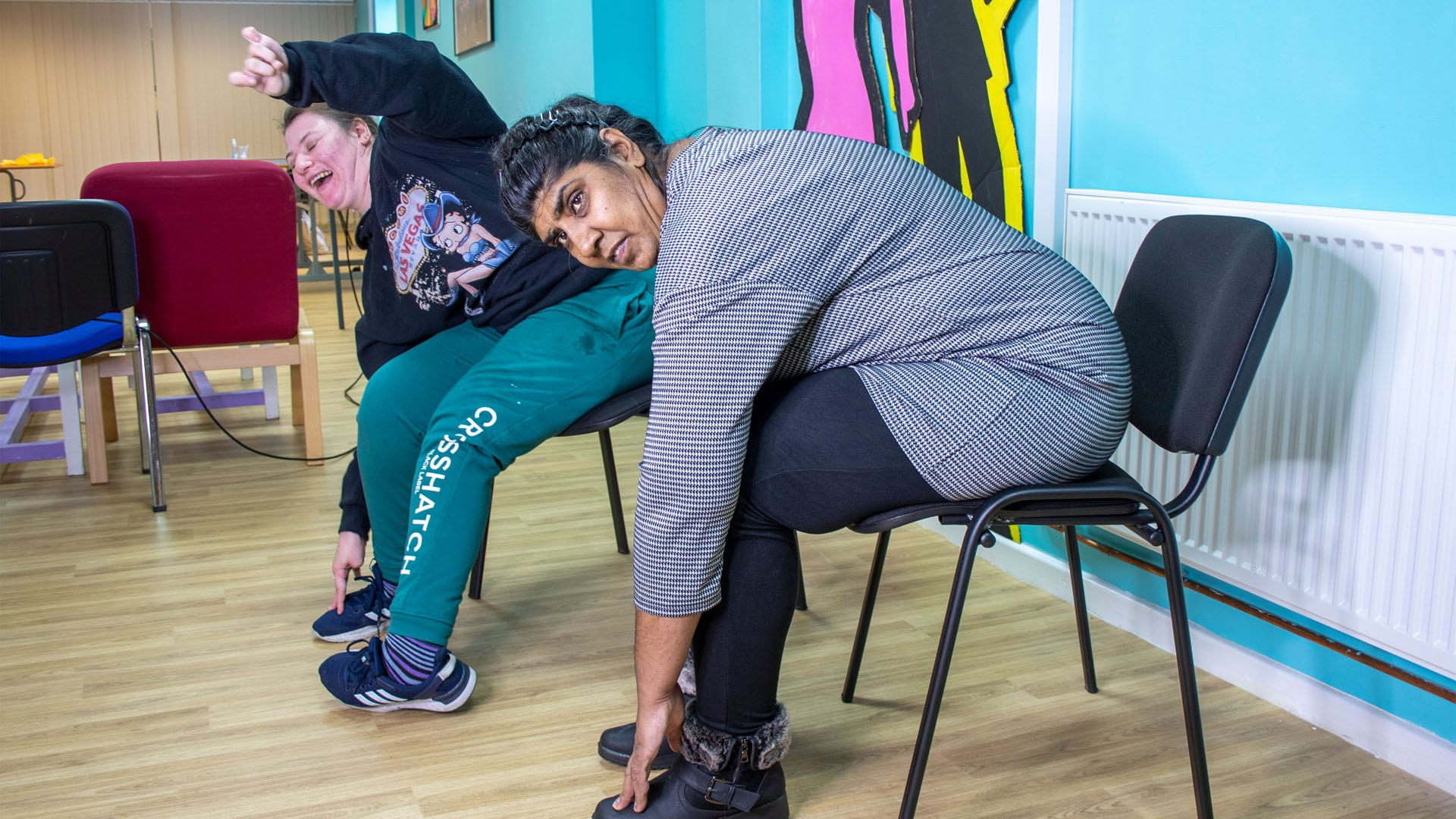 Two service users sat in chairs doing exercises.