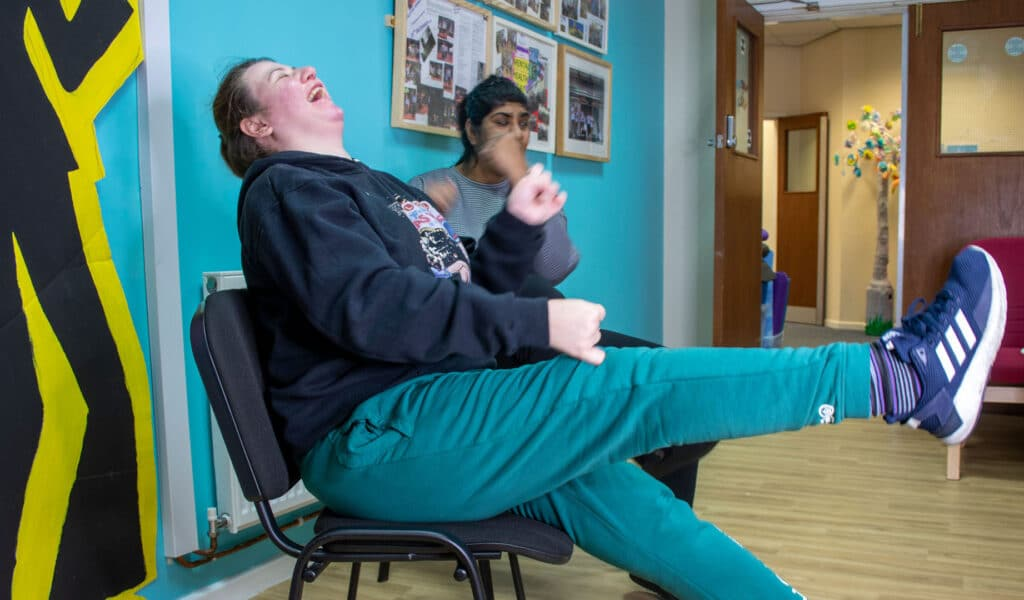 Two service users sat laughing together
