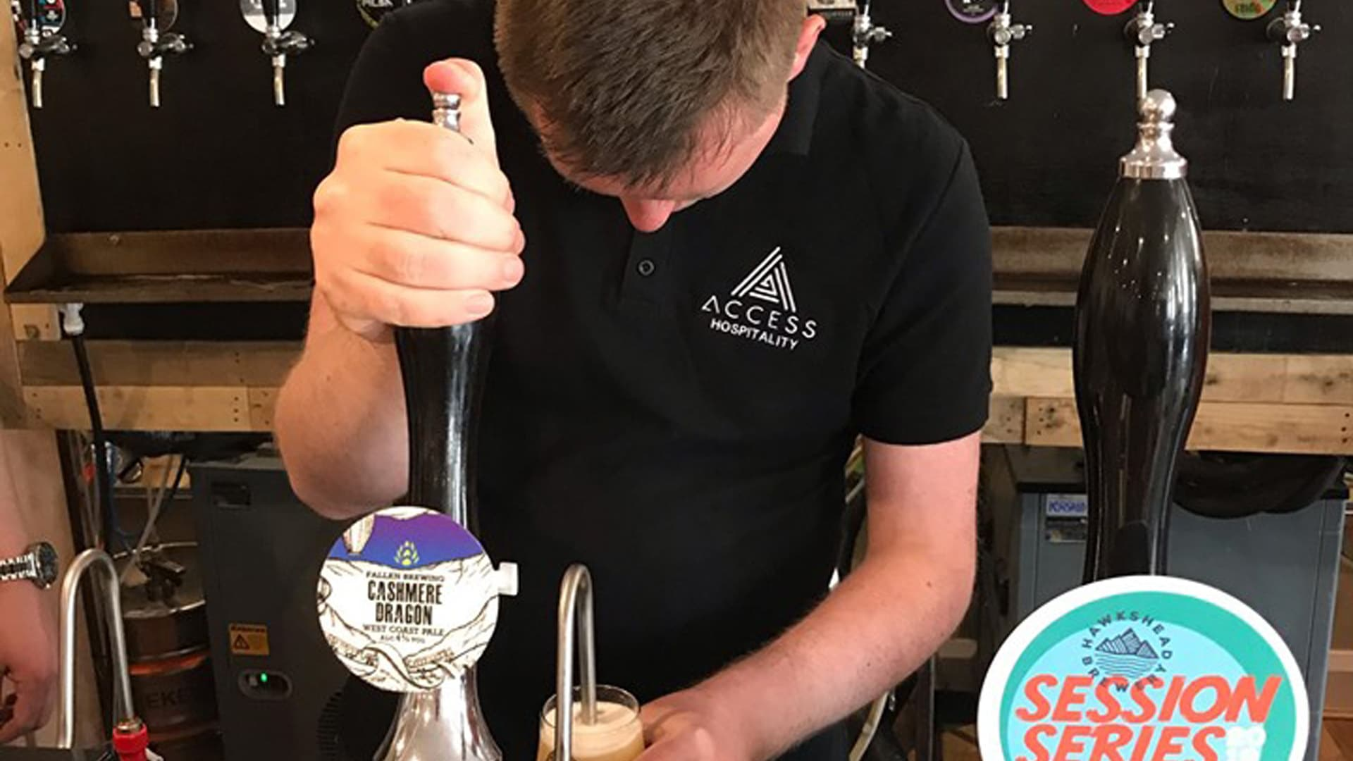 Pennine Magpies member wearing an Access Hospitality t-shirt, standing behind a bar, pulling a pint