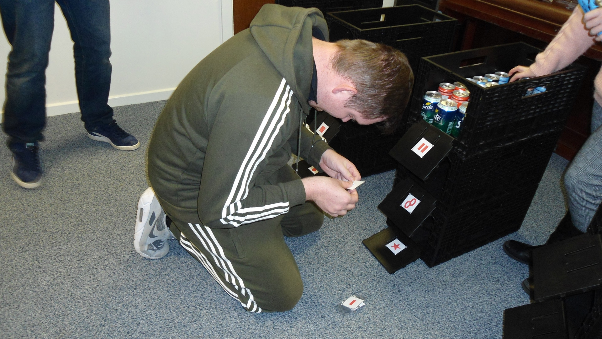 Magpies member looking at labels on crates of fizzy drinks