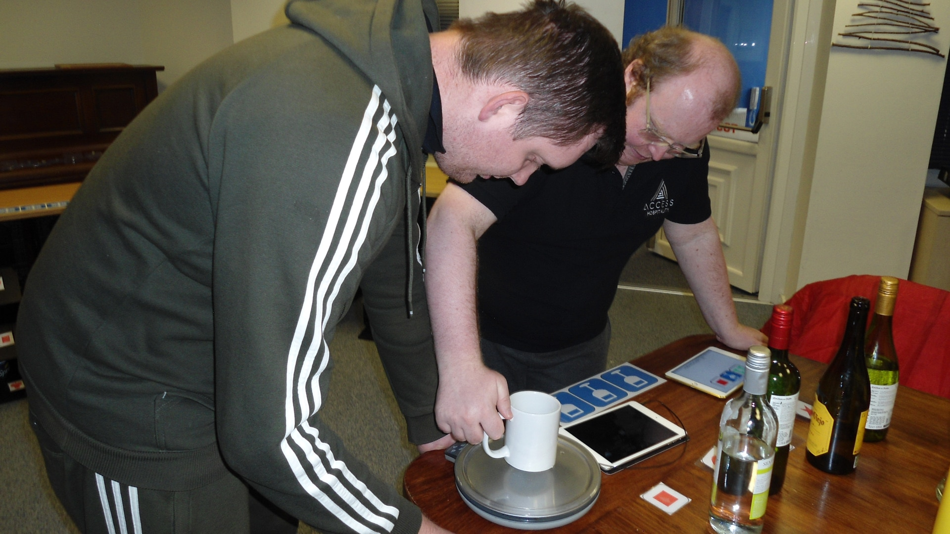 Magpies member holding a mug on a set of scales with bottles of wine, learning about drinks measurements