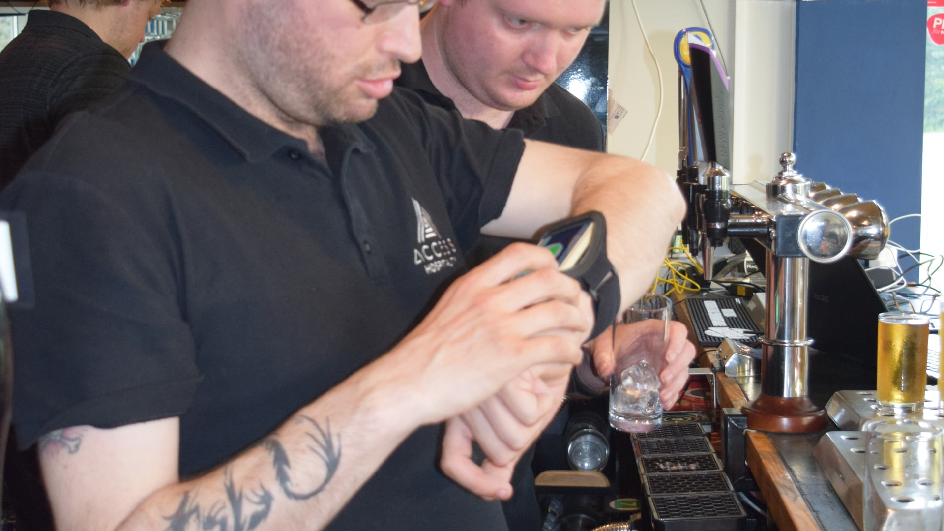 Magpies members behind a bar using smart devices around their wrists